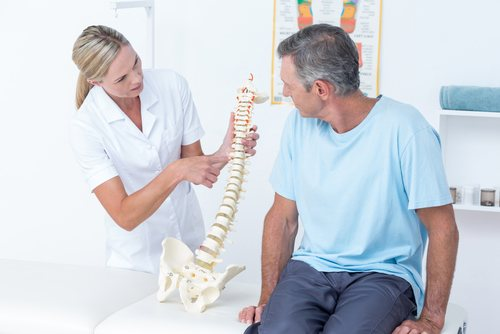 Physical therapist showing spine model to patient